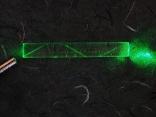 A laser bouncing down an acrylic rod, illustrating the total internal reflection of light in a multi-mode optical fiber.